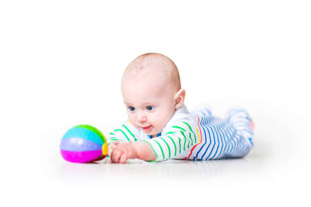 time: Happy laughing funny baby boy wearing a colorful shirt learning to crawl playing on his tummy, on white background Stock Photo