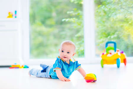 boy ball: Adorable baby boy playing with a colorful ball and toy car in a sunny nursery with white furniture and white floor and a big garden view window