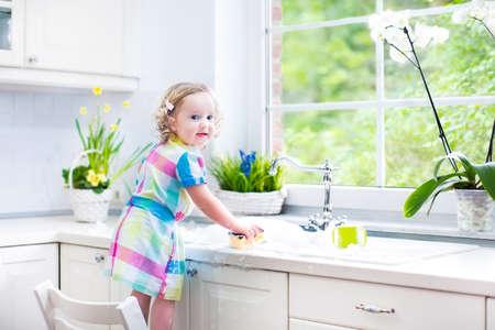 wash dishes: Niña niño lindo rizado en un colorido vestido de lavar los platos, limpiar con una esponja y jugando con espuma en el lavabo en una hermosa cocina blanco soleado, con una ventana con vistas al jardín en una casa moderna