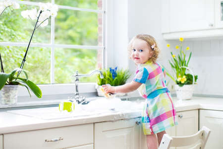 window cleaning: Cute curly toddler girl in a colorful dress washing dishes, cleaning with a sponge and playing with foam in the sink in a beautiful sunny white kitchen with a garden view window in a modern home