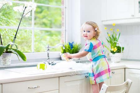 Leuk krullend peuter meisje in een kleurrijke jurk afwassen, schoonmaken met een spons en spelen met schuim in de gootsteen in een mooie zonnige witte keuken met een raam uitzicht op de tuin in een modern huis