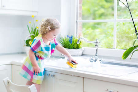 counter top: Cute curly toddler girl in a colorful dress washing dishes, cleaning with a sponge and playing with foam in the sink in a beautiful sunny white kitchen with a garden view window in a modern home