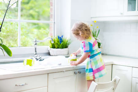 Cute curly toddler girl in a colorful dress washing dishes, cleaning with a sponge and playing with foam in the sink in a beautiful sunny white kitchen with a garden view window in a modern home   photo