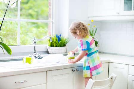 Niña niño lindo rizado en un colorido vestido de lavar los platos, limpiar con una esponja y jugando con espuma en el lavabo en una hermosa cocina blanco soleado, con una ventana con vistas al jardín en una casa moderna