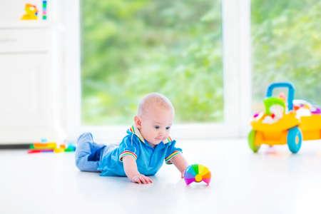 Neonato adorabile che gioca con una macchina palla e giocattolo colorato in un vivaio di sole con mobili bianchi e pavimento bianco e una finestra vista grande giardino Archivio Fotografico - 30781216
