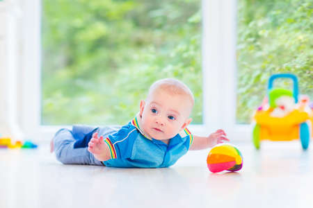 play room: Adorable baby boy playing with a colorful ball and toy car in a sunny nursery with white furniture and white floor and a big garden view window