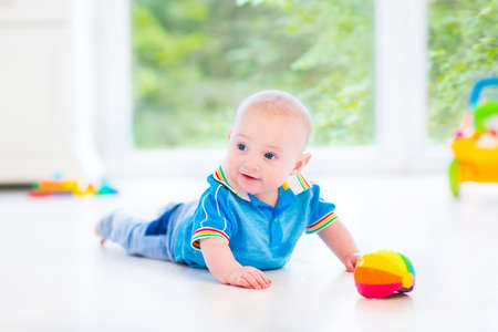 first floor: Adorable baby boy playing with a colorful ball and toy car in a sunny nursery with white furniture and white floor and a big garden view window