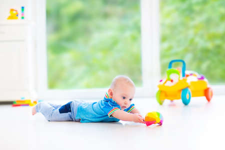 Adorable baby boy playing with a colorful ball and toy car in a sunny nursery with white furniture and white floor and a big garden view window   photo