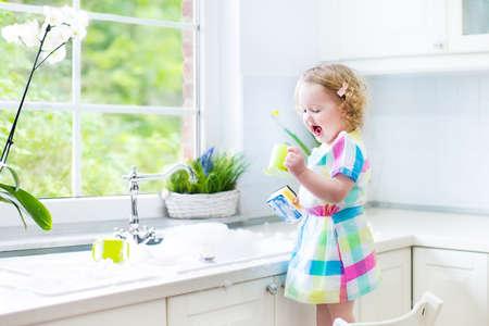 Leuk krullend peuter meisje in een kleurrijke jurk afwassen, schoonmaken met een spons en spelen met schuim in de wastafel in een mooie zonnige witte keuken met een raam uitzicht op de tuin in een modern huis Stockfoto