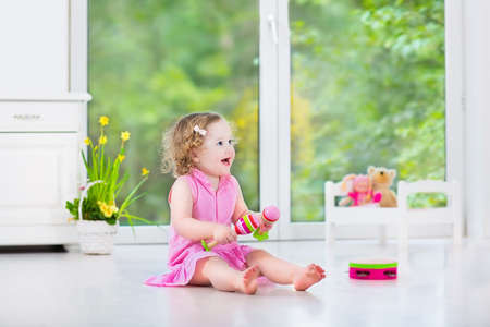 Cute curly laughing toddler girl in a pink dress playing tambourine and maracas in a sunny room with a big garden view window with a toy bed and spring flowers next to her, white modern interior home   Stock Photo