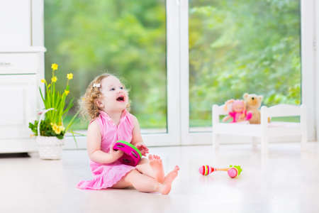 Cute curly laughing toddler girl in a pink dress playing tambourine and maracas in a sunny room with a big garden view window with a toy bed and spring flowers next to her, white modern interior home   Archivio Fotografico