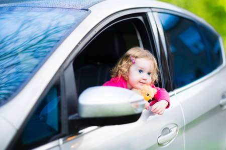 Adorable laughing curly toddler girl playing with toy teddy bear sitting in a silver color modern family car on front seat watching out a window in a side mirror enjoying weekend vacation ride after rain   photo