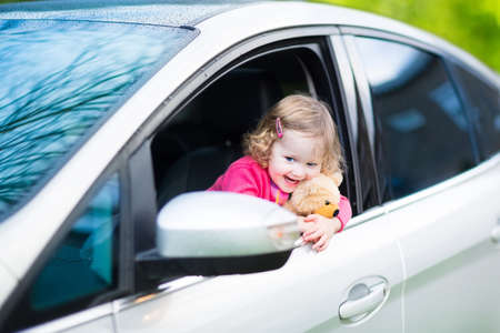 car front: Cute laughing curly toddler girl playing with toy teddy bear sitting in a silver color modern family car on front seat watching out a window in a side mirror enjoying weekend vacation ride after rain