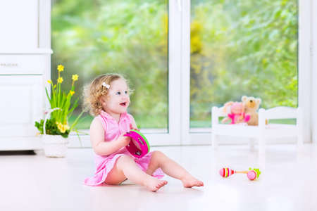 Cute curly laughing toddler girl in a pink dress playing tambourine and maracas in a sunny room with a big garden view window with a toy bed and spring flowers next to her, white modern interior   photo