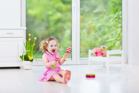 tambourine: Cute curly laughing toddler girl in a pink dress playing tambourine and maracas in a sunny room with a big garden view window with a toy bed and spring flowers next to her, white modern interior