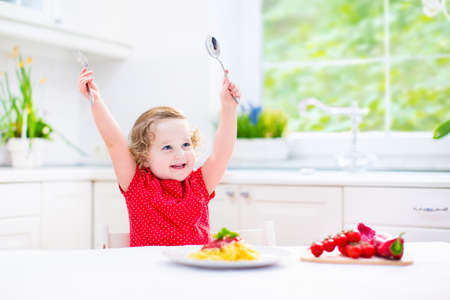 people eating restaurant: Cute curly laughing toddler girl in a red shirt playing with fork and spoon eating spaghetti with tomato sauce and vegetables for healthy lunch sitting in a white sunny modern kitchen with big window  Stock Photo