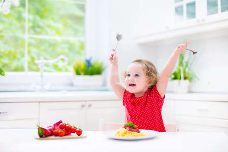 Cute curly laughing toddler girl in a red shirt playing with fork and spoon eating spaghetti with tomato sauce and vegetables for healthy lunch sitting in a white sunny modern kitchen with big window  photo