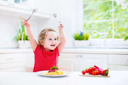 messy kitchen: Cute curly laughing toddler girl in a red shirt playing with fork and spoon eating spaghetti with tomato sauce and vegetables for healthy lunch sitting in a white sunny modern kitchen with big window  Stock Photo