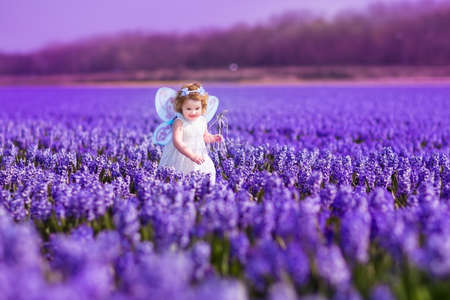 Portrait of an adorable toddler girl in a magic fairy costume and flower crown in her curly hair playing with a wand in a beautiful field of purple hyacinths in Keukenhof, Holland on windy spring day