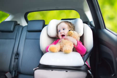 Cute curly laughing and talking toddler girl playing with a toy bear enjoying a family vacation car ride in a modern safe vehicle sitting in a baby seat with belt having fun watching out of the window   Stock Photo