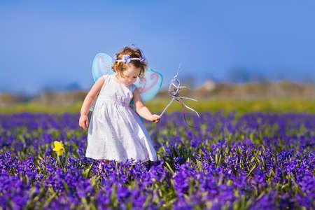 Portrait of an adorable toddler girl in a magic fairy costume and flower crown in her curly hair playing with a wand in a beautiful field of purple hyacinths in Keukenhof, Holland photo
