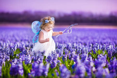 butterfly  angel: Portrait of an adorable toddler girl in a magic fairy costume and flower crown in her curly hair playing with a wand in a beautiful field of purple hyacinths in Keukenhof, Holland on windy spring day