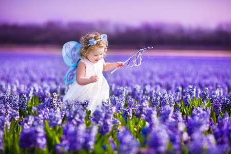 Portret van een schattig peuter meisje in een magische fee kostuum en bloem kroon in haar krullend haar spelen met een toverstaf in een prachtig gebied van paarse hyacinten in Keukenhof, Holland op winderige lentedag Stockfoto
