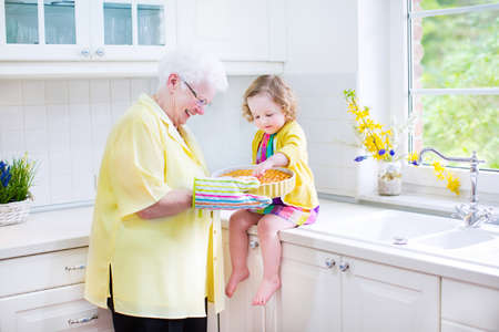Happy beautiful great grandmother and her adorable granddaughter, curly toddler girl in colorful dress, baking an apple pie together standing next to white oven in sunny modern kitchen with big window photo