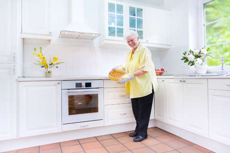the elderly residence: Beautiful fir and active senior lady baking a delicious apple pie in a sunny kitchen with modern furniture and white interior style, with a big window, oven and kitchen sink