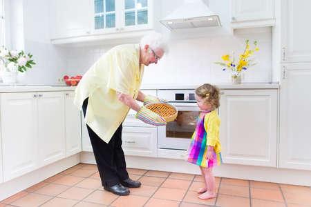 great grandmother: Feliz hermosa gran abuela y su nieta adorable, ni�o ni�a rizado en traje de colores, hornear un pastel de manzana juntos de pie junto a la estufa en la cocina moderna blanco soleado con ventana grande