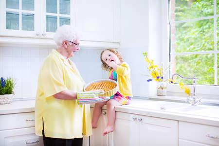Heureux belle grand-mère et sa petite-fille adorable, bouclés fille de bébé en robe colorée, la cuisson une tarte aux pommes ainsi debout à côté de four blanc dans la cuisine moderne ensoleillée avec grande fenêtre