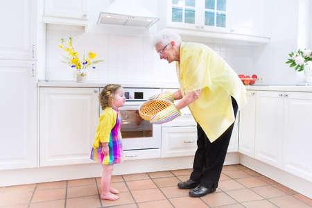 Heureux belle grand-mère et sa petite-fille adorable, bouclés fille de bébé en robe colorée, la cuisson une tarte aux pommes ainsi debout à côté de four blanc dans la cuisine moderne ensoleillée avec grande fenêtre Banque d'images
