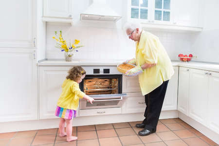 kitchen device: Happy grandmother and little girl baking a pie in a white kitchen Stock Photo