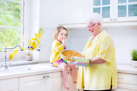 baking oven: Happy beautiful great grandmother and her adorable granddaughter, curly toddler girl in colorful dress, baking an apple pie together standing next to white oven in sunny modern kitchen with big window