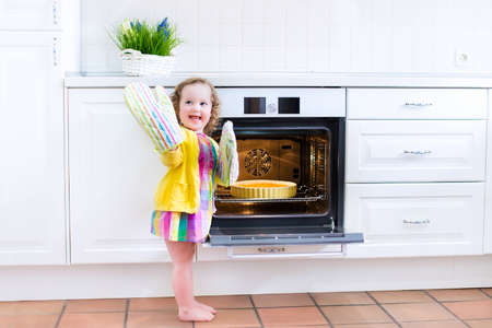 Adorable toddler girl in a yellow dress wearing colorful mittens playing in the kitchen next to a modern white oven helping by cooking and baking an apple pie in a home with white interior Stock Photo