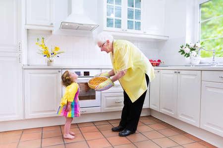 great grandmother: Feliz hermosa gran abuela y su nieta adorable, ni�o ni�a rizado lindo en un vestido de colores, hornear un pastel de manzana juntos de pie junto a un horno de blanco en una cocina moderna soleado con ventana grande