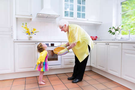 Happy beautiful great grandmother and her adorable granddaughter, cute curly toddler girl in a colorful dress, baking an apple pie together standing next to a white oven in a sunny modern kitchen with big window photo