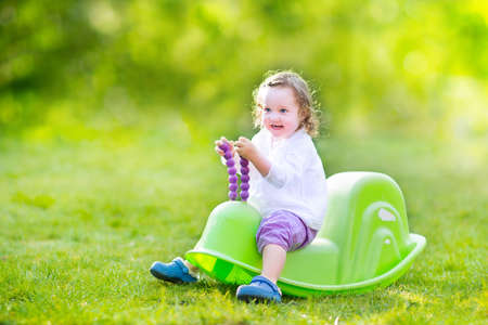 Adorable funny curly toddler girl playing in the garden, enjoying a swing ride, playing with plastic toys on the lawn on a sunny summer morning photo
