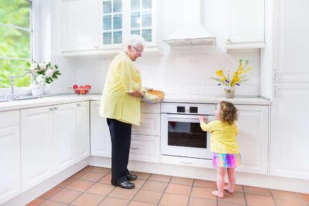 great grandmother: Feliz hermosa gran abuela y su nieta adorable, ni�o ni�a rizado en vestido de colores, hornear un pastel de manzana juntos de pie junto a la estufa blanca en la cocina moderna soleado con ventana grande