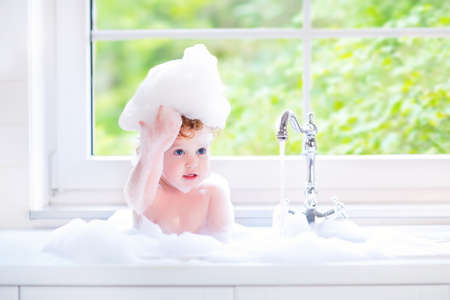 Funny little baby girl with wet curly hair taking a bath in a kitchen sink with lots of foam playing with water drops and splashes next to a big window with garden view photo