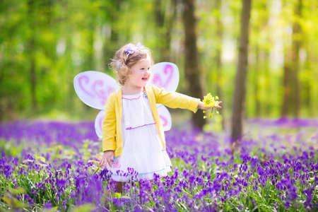 angeles bebe: Muchacha adorable del niño con el pelo rizado que llevaba un traje de hada con alas de color púrpura y vestido amarillo está jugando en un hermoso bosque de la primavera con las flores frescas campanilla florecimiento en un día soleado en el campo alemán