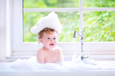 Funny little baby girl with wet curly hair taking a bath in a kitchen sink with lots of foam playing with water drops and splashes next to a big window with garden view Stock Photo