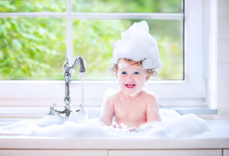 Funny little baby girl with wet curly hair taking a bath in a kitchen sink with lots of foam playing with water drops and splashes next to a big window with garden view 写真素材