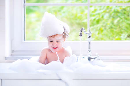 bubble bath: Funny little baby girl with wet curly hair taking a bath in a kitchen sink with lots of foam playing with water drops and splashes next to a big window with garden view Stock Photo