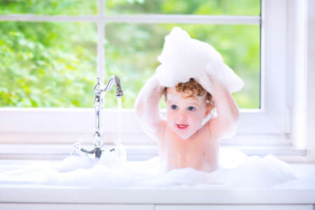 Funny little baby girl with wet curly hair taking a bath in a kitchen sink with lots of foam playing with water drops and splashes next to a big window with garden view Standard-Bild