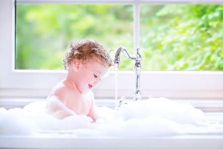 Funny little baby girl with wet curly hair taking a bath in a kitchen sink with lots of foam playing with water drops and splashes next to a big window with garden view Stockfoto