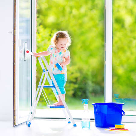 kitchen device: Cute laughing curly toddler girl washing a big window with a squeegee in beautiful white living room with door into the garden, standing on a ladder next to a blue bucket with water, detergent solution spray bottle and sponge Stock Photo