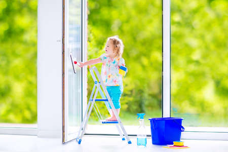 window cleaning: Cute laughing curly toddler girl washing a big window with a squeegee in beautiful white living room with door into the garden, standing on a ladder next to a blue bucket with water, detergent solution spray bottle and sponge Stock Photo