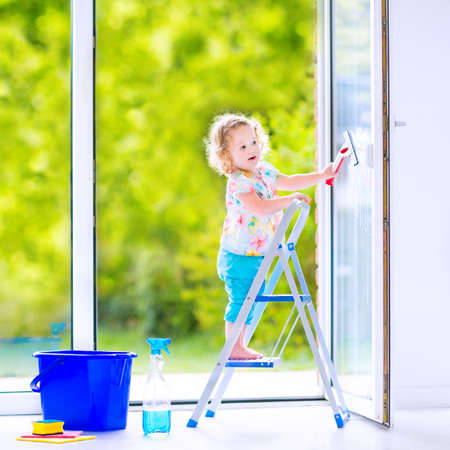 the window: Cute laughing curly toddler girl washing a big window with a squeegee in beautiful white living room with door into the garden, standing on a ladder next to a blue bucket with water, detergent solution spray bottle and sponge Stock Photo