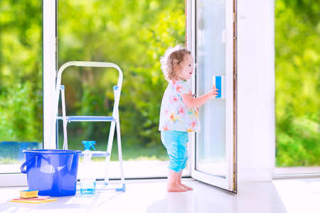 Cute laughing curly toddler girl washing a big window with a squeegee in beautiful white living room with door into the garden, standing on a ladder next to a blue bucket with water, detergent solution spray bottle and sponge photo